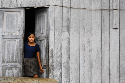 A girl gazes out of her front door, keeping an eye on younger brothers and sisters, in the tiny Amazon village of Nuevo Rocafuerte at the border between Peru and Ecuador.