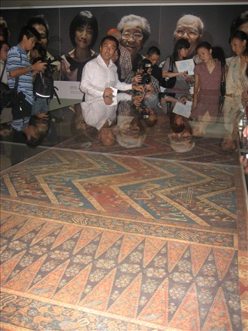 Museum curator showing us one of the world's oldest batik textiles