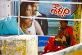 A woman sits beneath a Bollywood billboard, lost in thought as her baby is quietly sick.: by lauretta_j, Views[132]