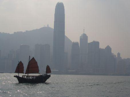 Barco tradicional passando na frente do prédio mais alto de HK.