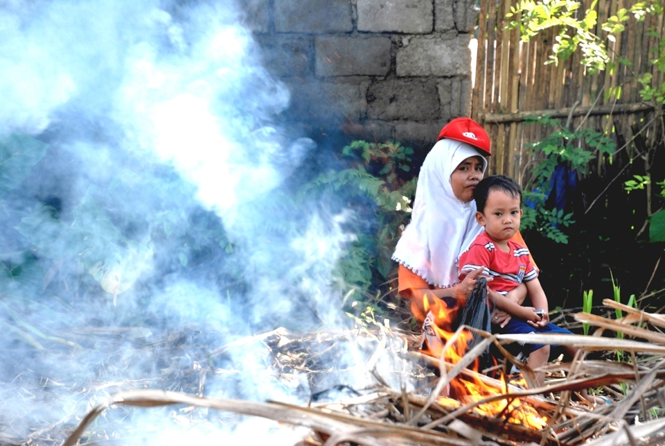 Mrs. Nik and her son, Rofiq, waits in the shades while Mr. Nik works on burning the remaining cane plants after the harvest.