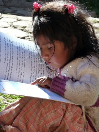 A young girl from the weaving community of Amaru, Peru learns how to read. Weavers and families, together, described lack of access to most amenities and services as a result of distance and isolation of the community and raised concern for high illiteracy rates in the community. The community requested literacy training as a Volunteer Service Project.