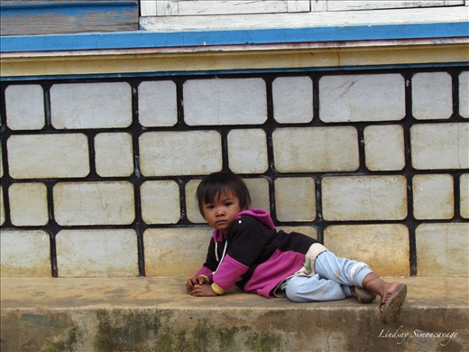 A young Lat minority boy near Dalat resting on the stairs
