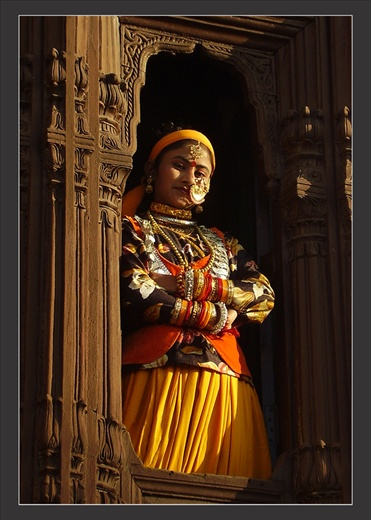 After a day's hard work these women dress themselves in traditional attires especially on the occasion of some celebration. Here such a girl looks confidently from window of home - Uttranchal