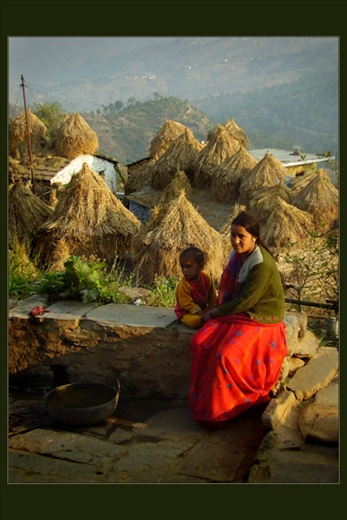 Motherhood, every woman's dream. Despite all adversities of their life women make great effort to bring up their children. Here a proud mother enjoys sun with her chils in a village. - Uttranchal