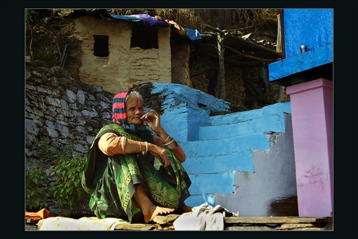 Here an old woman enjoys some moments contemplating her life. The people of Uttranchal like to paint their humble houses in multi colours and people, especially women wear very colourful clothes. The colourful blue steps convey the sense of happiness and calm in life, and mauve pillar adds vigour - Uttranchal