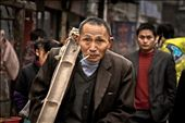 A laborer walks down a busy Zhangjiajie street with his biandan (two baskets and bamboo pole) slung casually over his shoulder and a cigarette dangling effortlessly from the corner of his mouth. : by littletrades, Views[549]