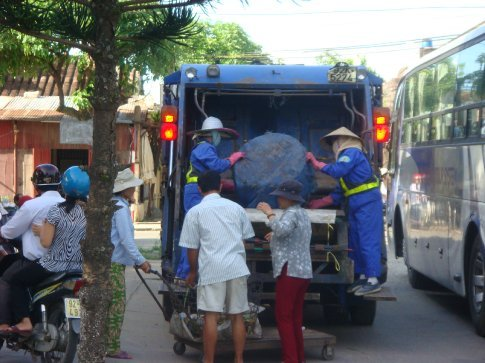The garbage truck rolls through the city streets in the morning playing a little gingle not unlike the ice cream man.  Everyone runs out of their homes and shops when the garbage man rolls through.