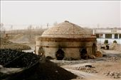 In Ordos Basin, a brick-firing hut. Coal fuel piled in the foreground, with finished brick piled in the back. This structure gives no indication of its age to the traveler looking on from bus.: by lkubiak, Views[433]