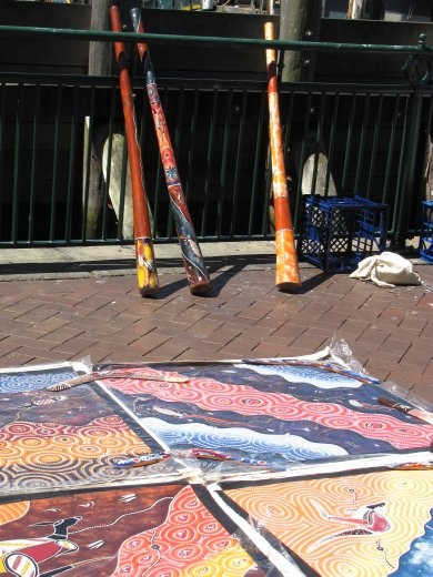 Dideridoo and aboriginal artwork for sale on the pavement.