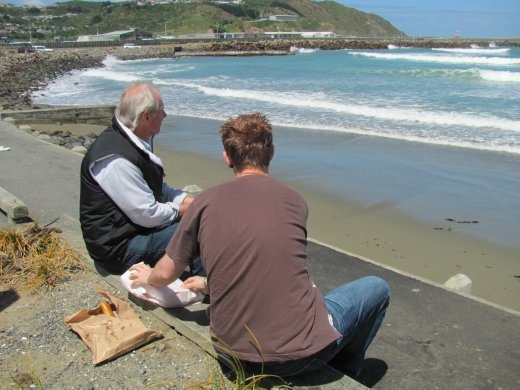 Greg and Andre having fish and chips at blustery Lyall Bay
