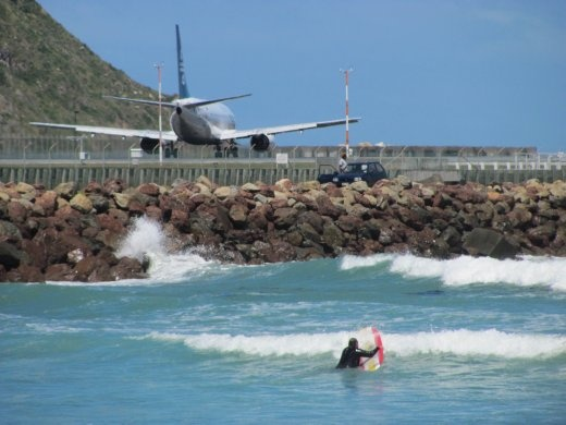 Surfers coming in next to aircraft at Lyall Bay, Wellington.