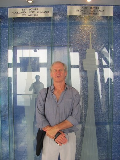 Greg up against glass engravings of other Telecom towers around the world - and their heights
