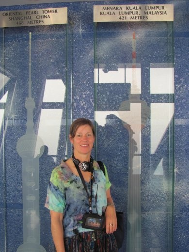Karen standing against the glass engravings of other Telecommunication towers around the world