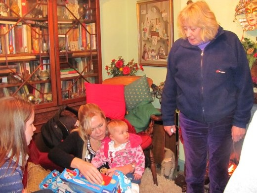 Sister Bev gives pressie to great niece Eleanor. Krissy's holding Eleanor whilst mother Kirsty looks on from the left.