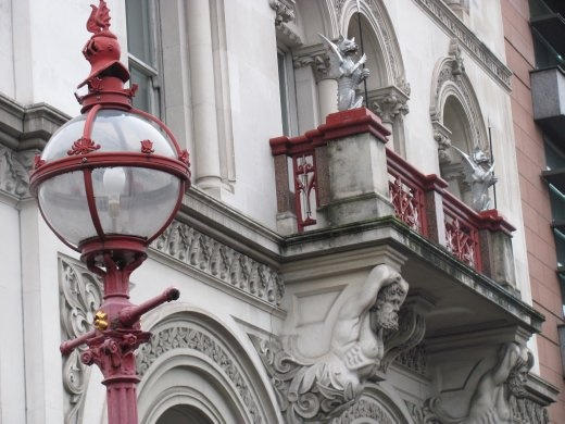 Lamp and edifice of a staircase leading down to the street below this bridge.