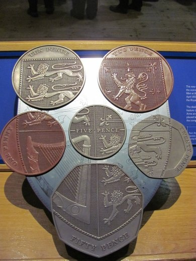 Display of the modern English coins. They all have part of the heraldry that completes a royal emblem, as depicted here.