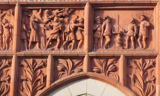 Some of the artwork on the red, brick building - showing medieval scenes.