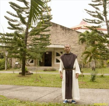 Brother Peter, a Trappist monk, poses in front of the Abbey Church