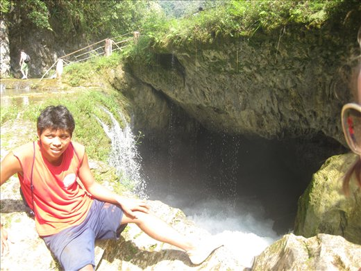 our tour guide sitting at the mouth of where the river goes under the waterfall