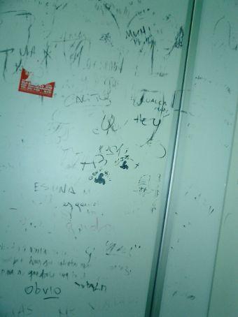 Back of toilet graffiti, in Spanish.