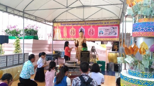 Phra Pathom Chedi School - Worshippers applying gold leaf to statue