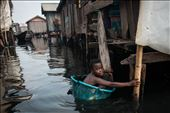 A young boy swims in through dirty oily water of Nigeria's Makoko slum. 30 April: by makoko, Views[101]