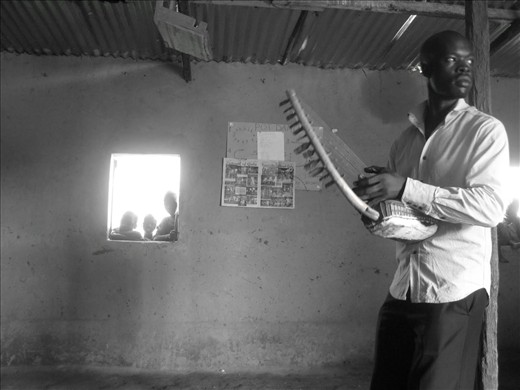 Morris, playing the bow-harp, waits for the Gulu Theatre Artists.