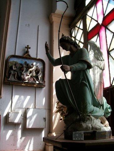 Detalhe: anjo e, na parede, um dos quadros da Via Sacra entalhados em madeira.