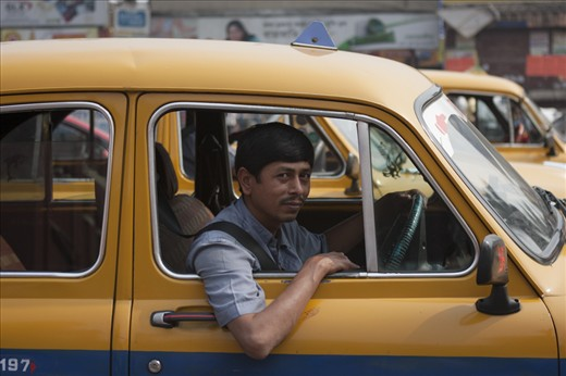 A driver of the typical yellow Kolkata taxis posing while in a traffic jam in Shyambazar area.