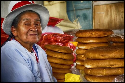 Vendedora de panes en un puesto del mercado de Cusco, Perú.