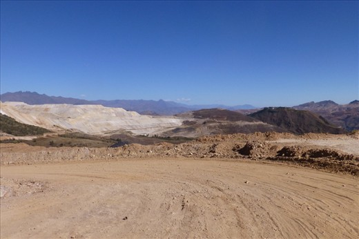 dirty road with a huge gold mine in the back ground.