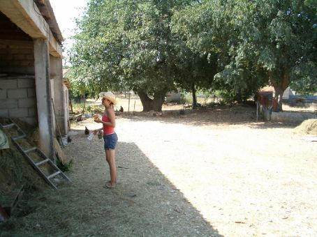 Maria trying to her best farmgirl impersonation in the yard at Policnik.