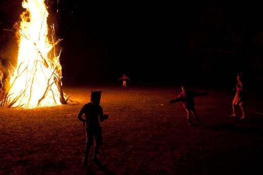 The festivities for the opening of the Summer Camp 2010. Children wearing Devil's horns dance by the bonfire to mark the occasion.