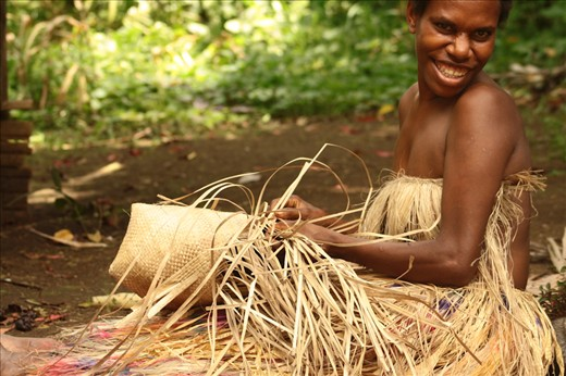 This young woman, living in a remote Kastom village in Tanna, where people still live according to millenary traditional customs, is weaving a basket with pandanus leaves. Lekalangia, Tanna, Vanuatu.