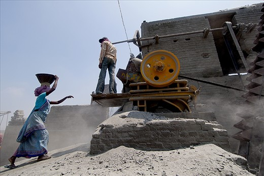 A women taking the stone to the crusher machine