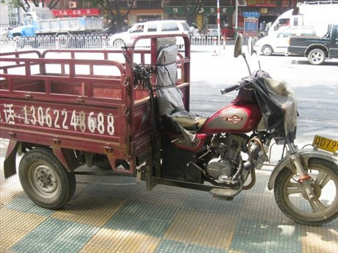 A dodgy three wheeled motorbike with a tray at the back.It's probably as old as the hills! :D