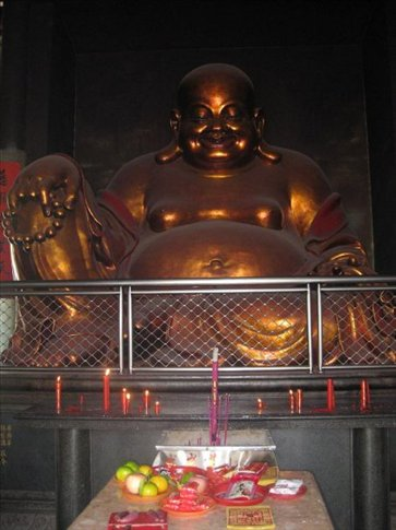 A giant 'Laughing Buddha' inside a Buddhist Temple in Longyan called The Lotus temple. On the table you can see incense and food for offerings. He looks quite happy with his loot! :D