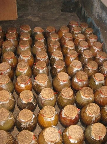 The rice wine bottled in the clay pots ready to be sold. You can see the dried banana leaves stretched over the top.