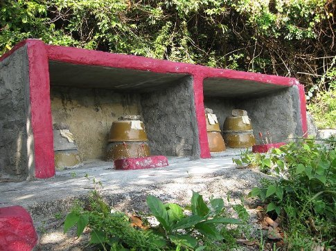 When I first saw these pots I thought they were just shrines, but I later discovered they are actually graves. The ashes of the deseced are inside andthe incense is to ward off evil sprits