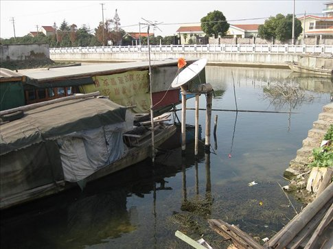 They might live in a rusty boat, but at least they have satellite tv. Zhujiajiao.