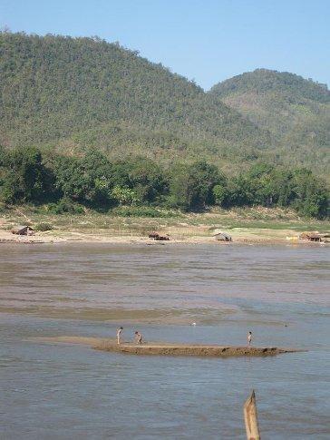 Chilrdren playing on a mud bank along the Mekong.