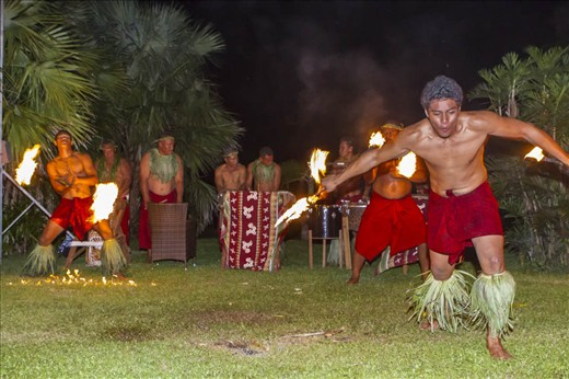 Samoan culture is highly social and here the use of the coconut tree leaves can be seen used for leg and neck decorations for the dancers and musicians performing the traditional fire dance at the end of an evenings meal and entertainment.