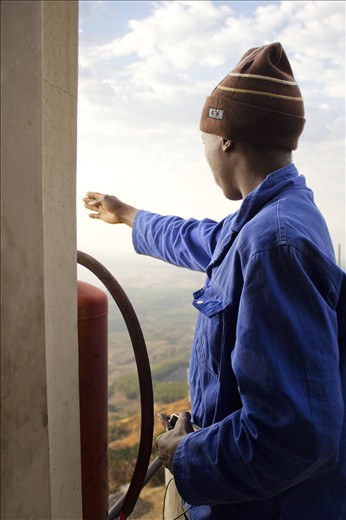 While explaining where the area's other three lookout posts are situated, Nelson Matsewjwa points into the direction of Nelspruit, Mpumalanga's capital city, South Africa. Standing at the top of the tower, Matsewjwa clutches onto his phone and a piece of