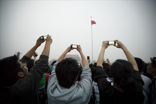 Consumer goods boom: Chinese tourists capture the lowering of the flag in Tiananmen Square, Beijing, on their smartphones. China has over one billion mobile phone subscribers, making it the world's largest mobile phone market. About 80% of the population uses a mobile phone, and about 45% of the population has internet access. Demand from the burgeoning middle class recently led China to surpass the US as the world's leading consumer of smartphones.