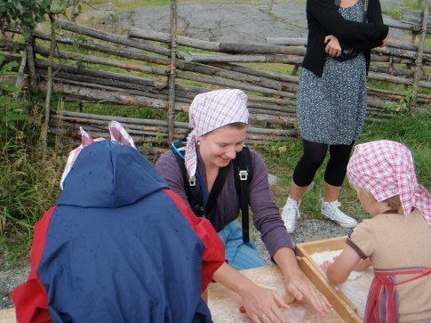 Em making Sami bread at Skansen, in the attire (+ the tourist things such as the camera).
