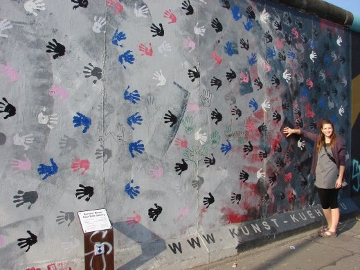 Em adding a hand print to another East Side Gallery painting.
