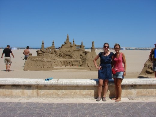 Em and Julz in front of an amazing sand castle at the beach in Valencia.