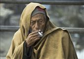 ..i was stuck in a traffic jam while in Kalimati, Nepal and was just observing the people around when i saw this man lighting up a cigarette to keep warm..: by myphotoscholarship2010, Views[198]