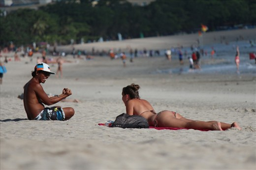 Local young man speaks with a tourist while she rests on the beach, in Bali, Indonesia.